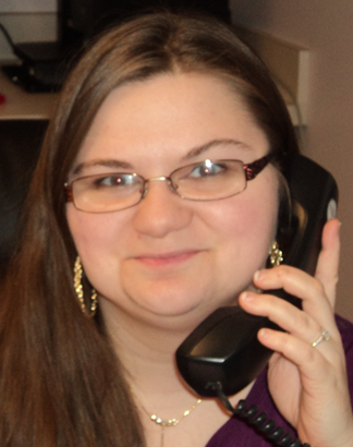 Angel Rhines -Long brown hair and glasses holding a telephone to her ear