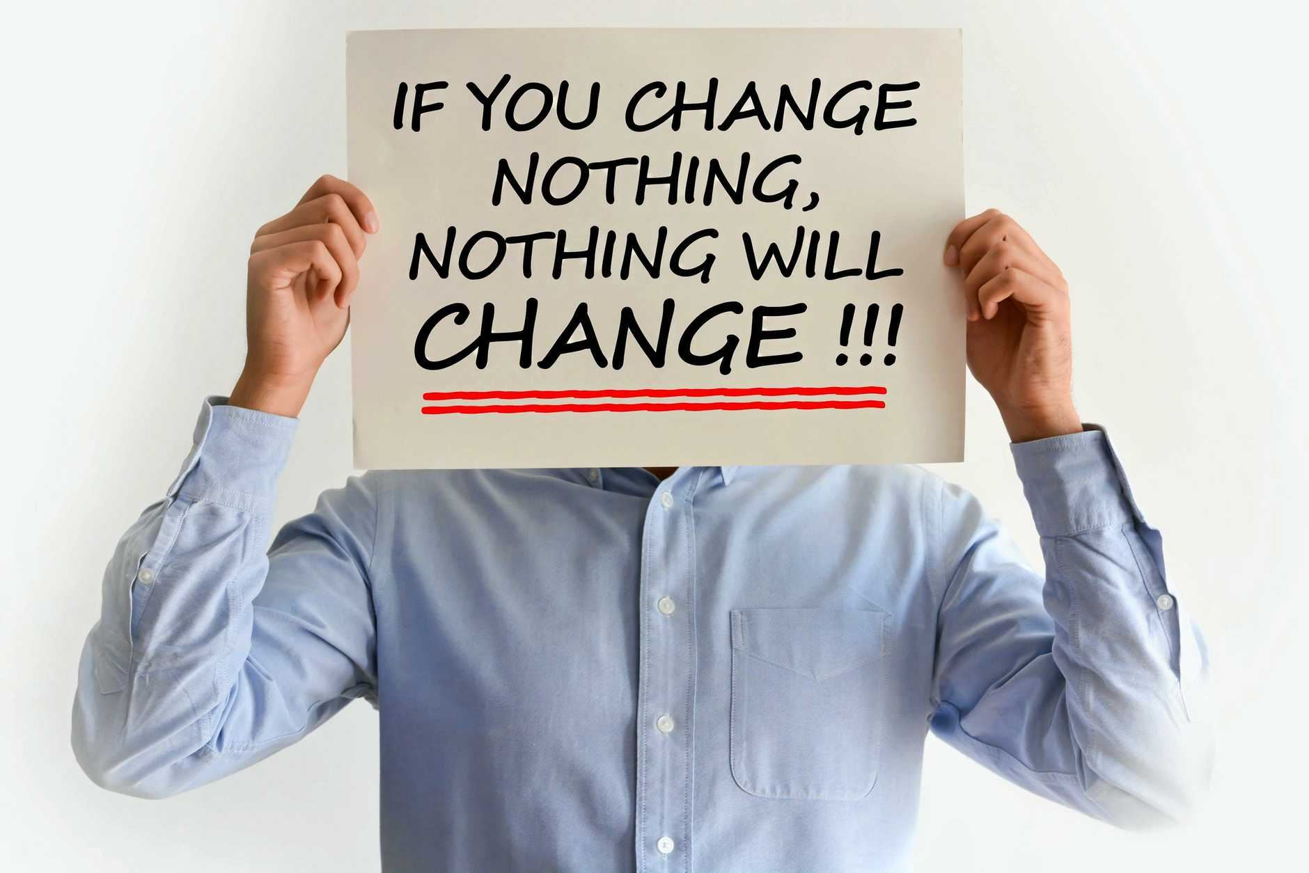 Person with long sleeve dress shirt holds a sign in front of their face that says. If you change nothing, nothing will change!!