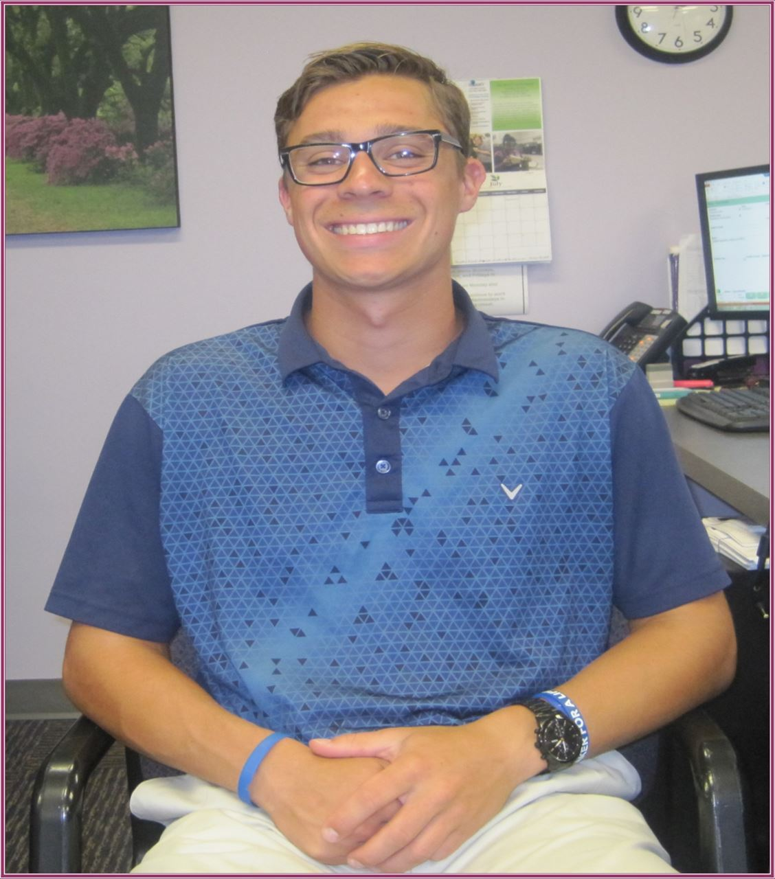 Young man wearing a two-toned collared blue shirt with glasses on, smiling, sits in an office chair with his hands folded in his lap