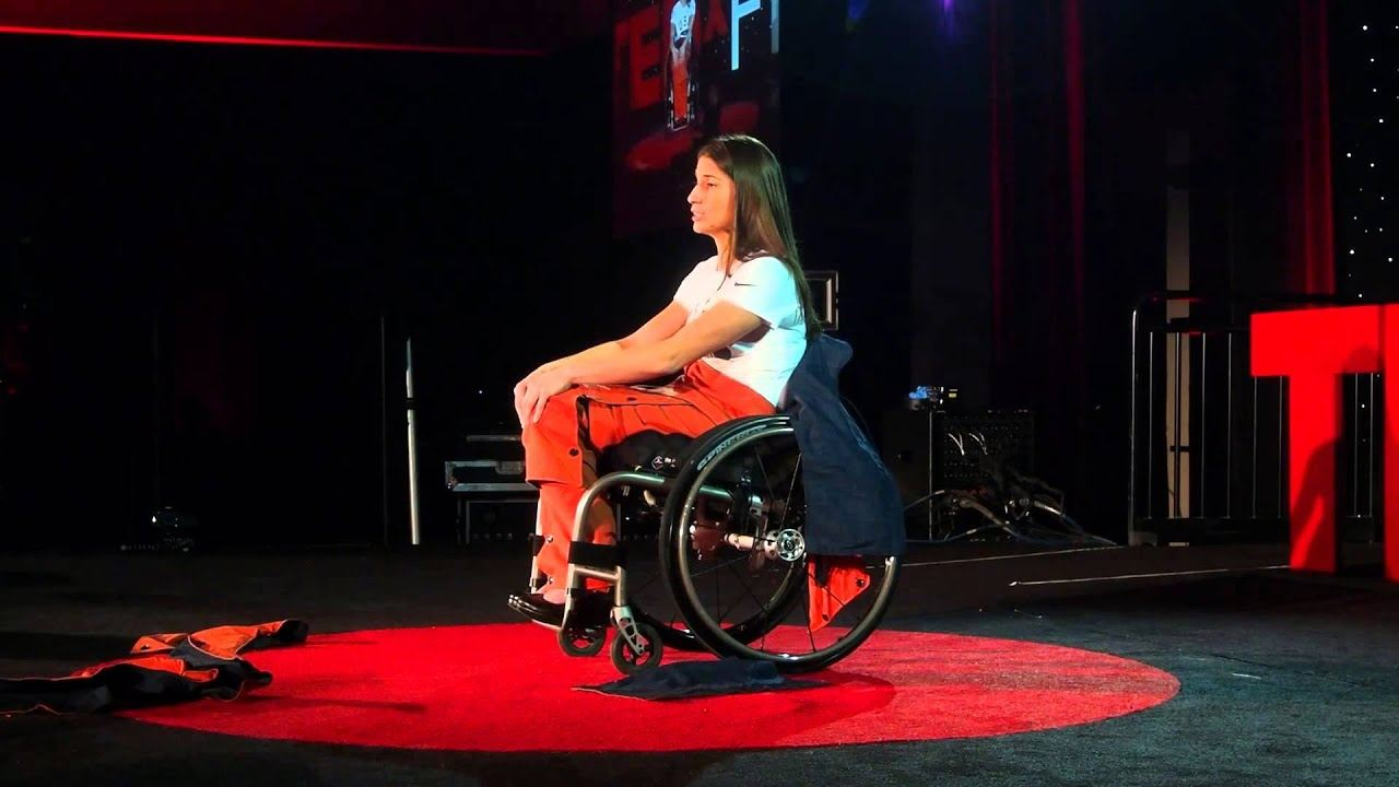 Ileana wears a white tee shirt, red pants and heels sits in her wheelchair on the stage at 2012 Ted Talks
