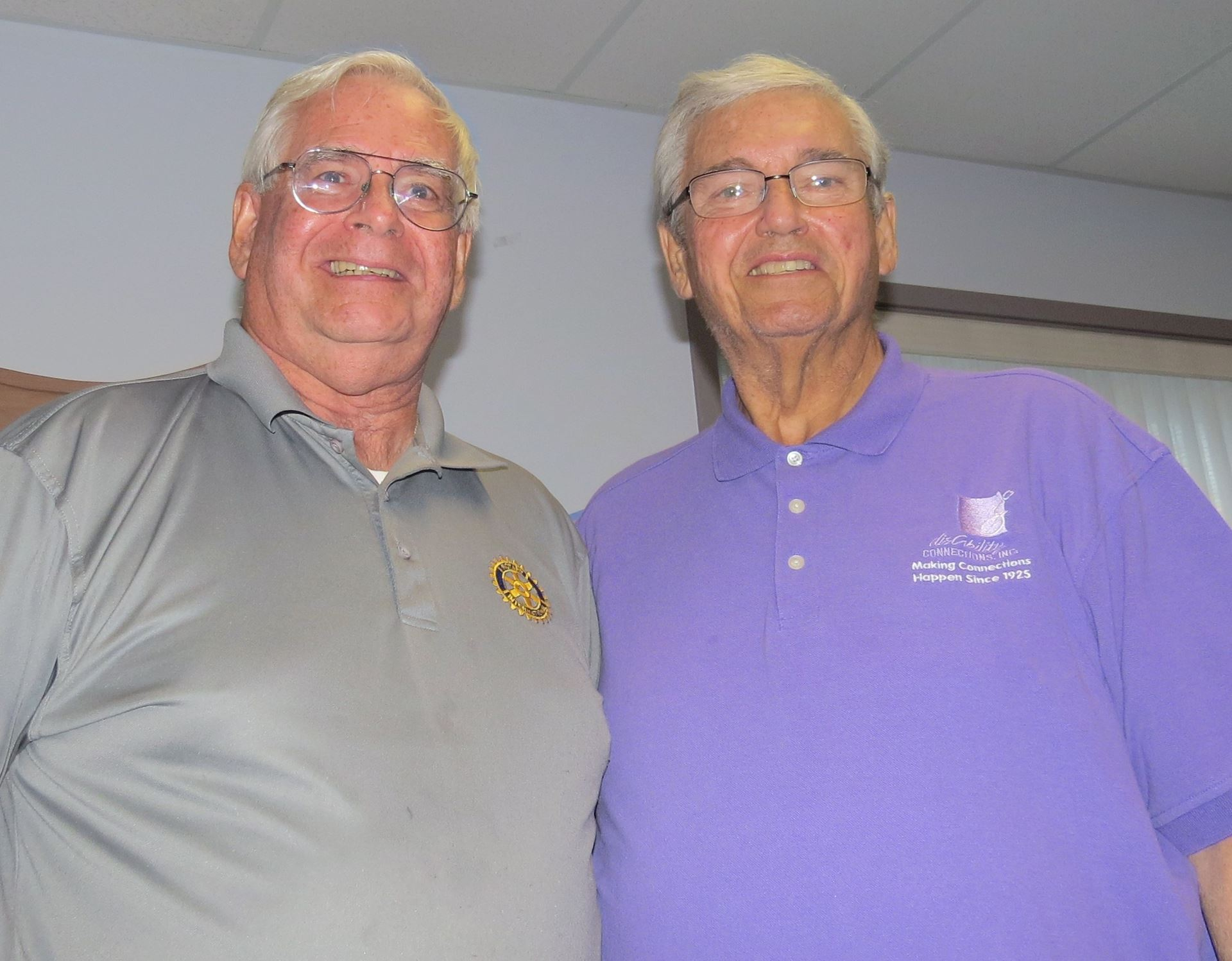 two older men stand side by side and smile down towards a camera. The man on the left wears a grey collared shirt, glasses and has short white hair. The man on the right also has short white hair, glasses, but is wearing a short sleeved collared purple shirt