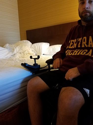 man in power chair sitting beside hotel bed to compare heights
